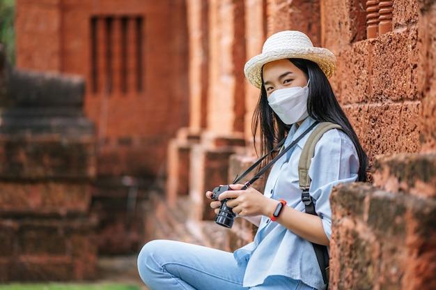 Jovem mochileira asiática usando chapéu e máscara de proteção enquanto viaja em local histórico