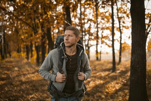 Jovem mochileiro andando na floresta de outono