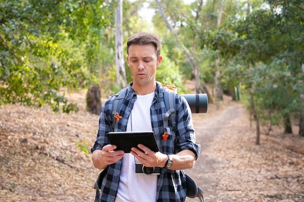 Jovem mochileiro caminhando, segurando o tablet e olhando para o mapa. viajante atraente caucasiano andando na estrada na floresta. turismo de mochila, aventura e conceito de férias de verão