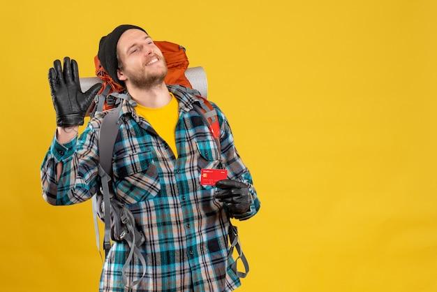 Jovem mochileiro com chapéu preto segurando um cartão de crédito na mão