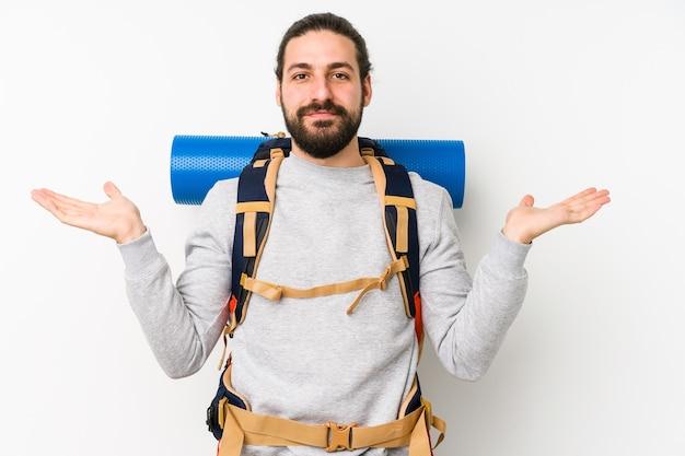 Jovem mochileiro isolado em um fundo branco faz escala com os braços, sente-se feliz e confiante.
