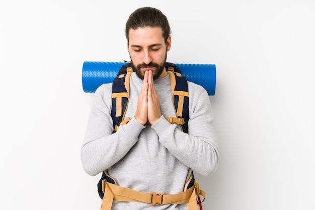 Jovem mochileiro isolado em um fundo branco, orando de mãos dadas perto da boca, sente-se confiante.