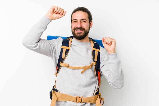 Jovem mochileiro isolado em uma parede branca comemorando um dia especial, pula e levanta os braços com energia.