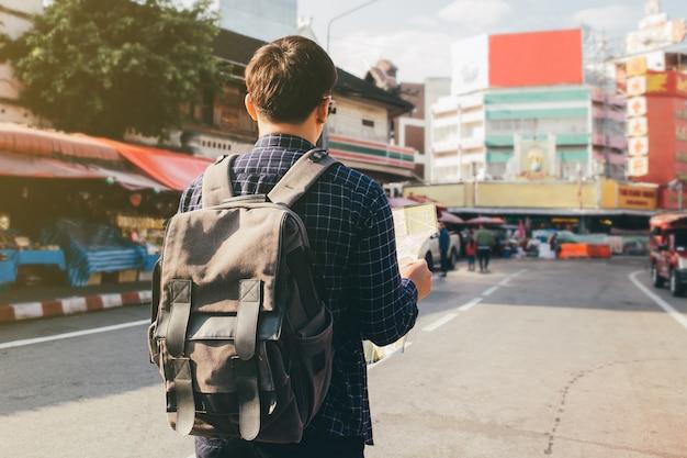 Jovem mochileiro viajante olha procurando direção no mapa de localização enquanto viaja para o exterior no verão