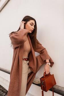 Jovem moda europeia com casaco longo e elegante em calças bege da moda com bolsa de couro marrom na moda perto de edifício vintage branco. modelo de menina elegante endireita o cabelo ao ar livre na rua.