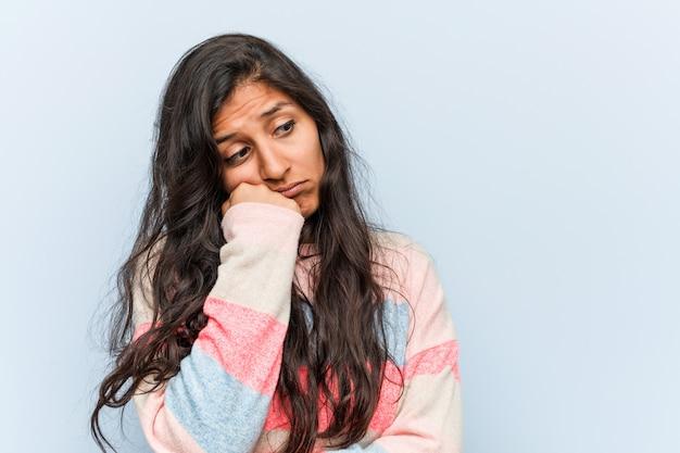 Jovem moda mulher indiana que se sente triste e pensativa, olhando para a cópia.