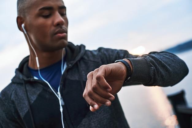 Jovem modelo africano olha para seu smartwatch para rastrear a distância que ele correu