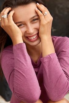 Jovem modelo alegre com sorriso agradável, mantém as mãos no rosto, estando em alto astral