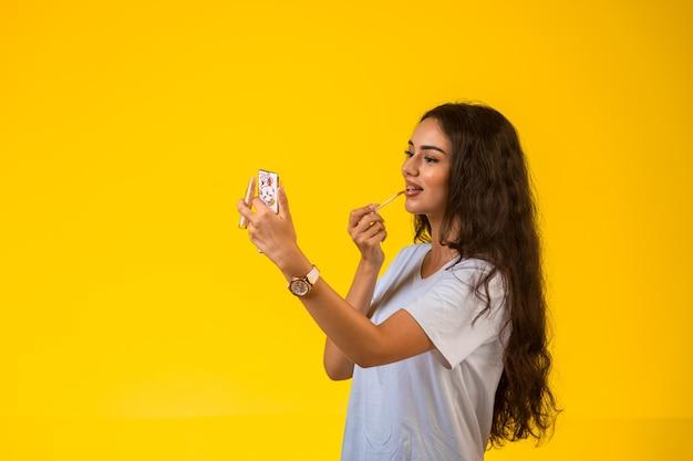 Jovem modelo aplicando brilho labial e olhando no espelho.