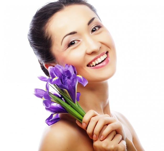 Jovem modelo asiático com flores de íris.
