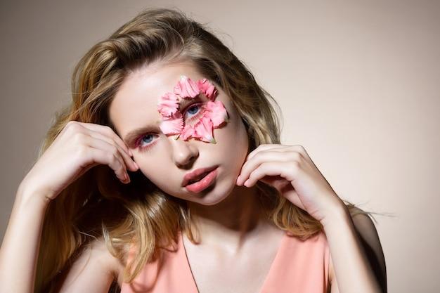 Jovem modelo atraente posando perto de uma parede de luz com pétalas de flores no rosto
