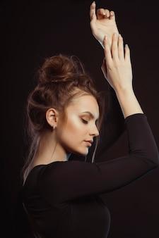 Jovem modelo carinhosa em um vestido preto posando no estúdio com os olhos fechados