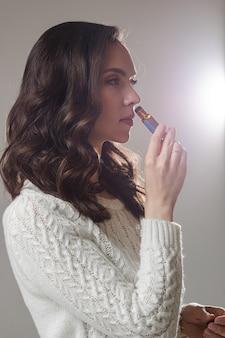 Jovem modelo caucasiana com longos cabelos escuros posa para a câmera com a mão perto do rosto