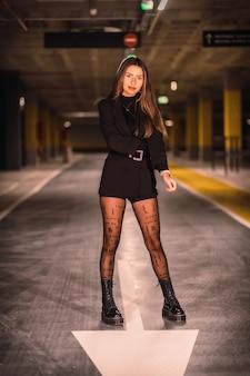 Jovem modelo caucasiano com jaqueta preta posando em um estacionamento subterrâneo vazio. sessão noturna urbana na cidade
