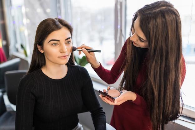 Jovem modelo com grandes olhos verdes está tendo o procedimento de maquiagem
