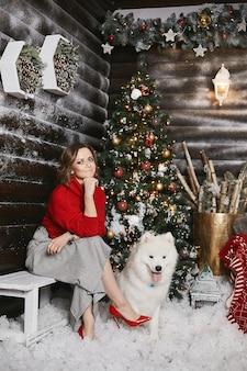 Jovem modelo com sapatos vermelhos e saia xadrez posando com cachorro fofo samoyed