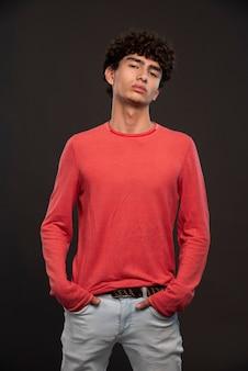 Jovem modelo de camisa vermelha, posando, colocando as mãos nos bolsos.