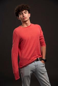 Jovem modelo de camisa vermelha posando com confiança no elenco.