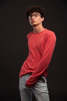 Jovem modelo de camisa vermelha, posando em peças fundidas.
