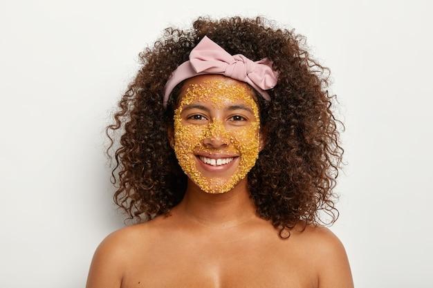 Jovem modelo de pele escura satisfeita usa ingredientes incríveis para a saúde da pele, tem grânulos de sal amarelos no rosto, usa todas as formas eficazes para ser bonita e jovem, abosrbs toxinas, tem procedimentos de higiene