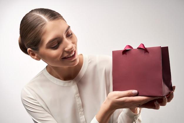 Jovem modelo demonstrando sacola de papel para presente