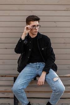 Jovem modelo descolado em roupas jeans elegantes endireita óculos da moda
