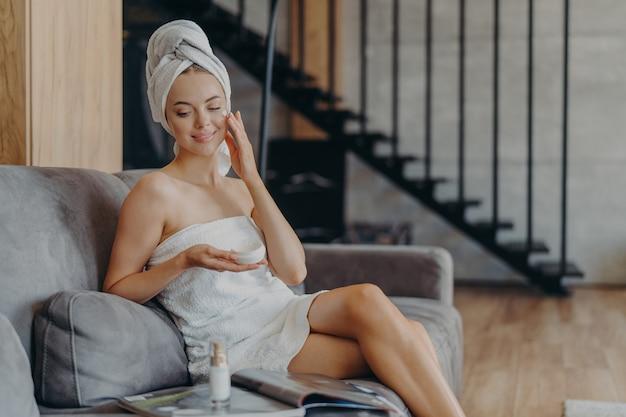 Jovem modelo feminina aplica creme no rosto, tem corpo perfeito, pele saudável e macia, senta-se em cômodo aconchegante no sofá, enrolada em toalha, lê revista, cuida da tez. cosmetologia e conceito de beleza