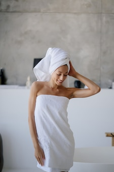 Jovem modelo feminina caucasiana relaxada em uma toalha branca