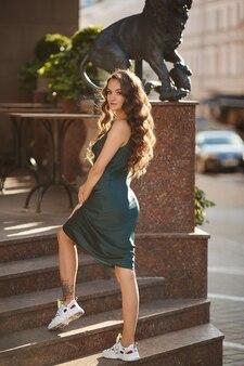 Jovem modelo feminina com um vestido de verão da moda e tênis posando na rua em um dia ensolarado de verão