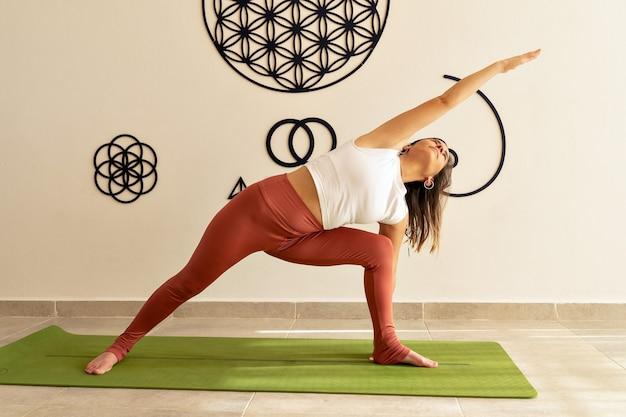 Jovem modelo feminina fazendo asanas de ioga no estúdio de ioga