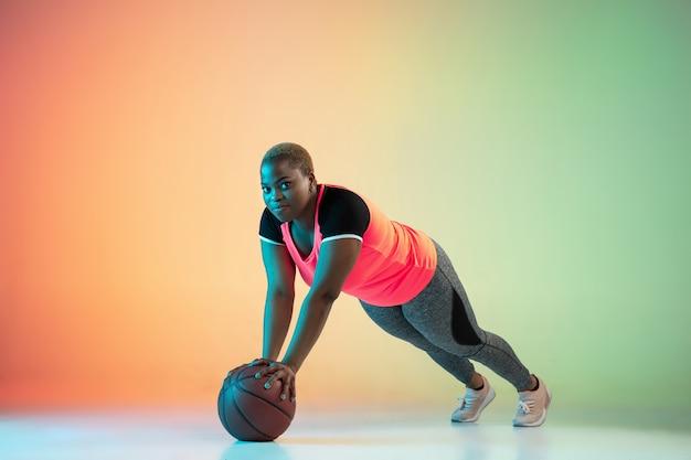 Jovem modelo feminino afro-americano plus size treinando em fundo gradiente