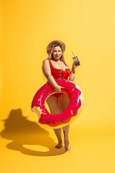 Jovem modelo feminino caucasiano plus size está preparando as férias na parede amarela. mulher de maiô vermelho e chapéu posando com natação.
