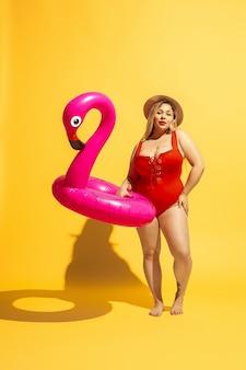 Jovem modelo feminino caucasiano plus size se preparando para um resort na praia em amarelo