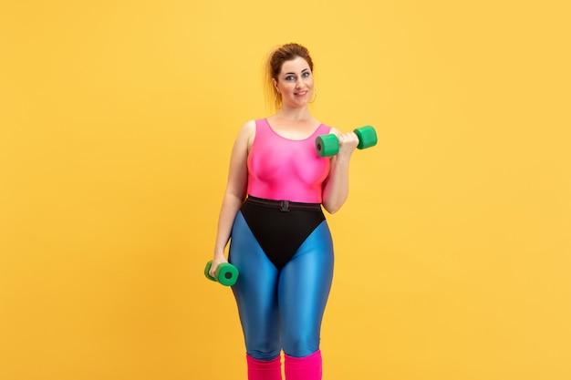 Jovem modelo feminino caucasiano plus size treinando em amarelo