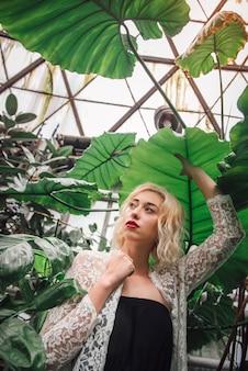 Jovem modelo feminino caucasiano rodeado com flora exótica