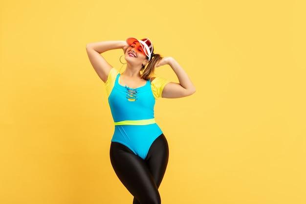 Jovem modelo feminino treinando na parede amarela