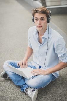 Jovem modelo hansome homem loiro com notebook e fones de ouvido