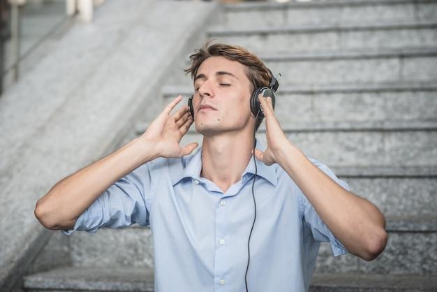Jovem modelo hansome loira com fones de ouvido