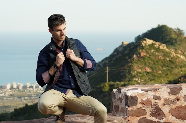 Jovem modelo hispânico usando uma camisa azul e uma jaqueta preta se passando perto de um muro de pedra