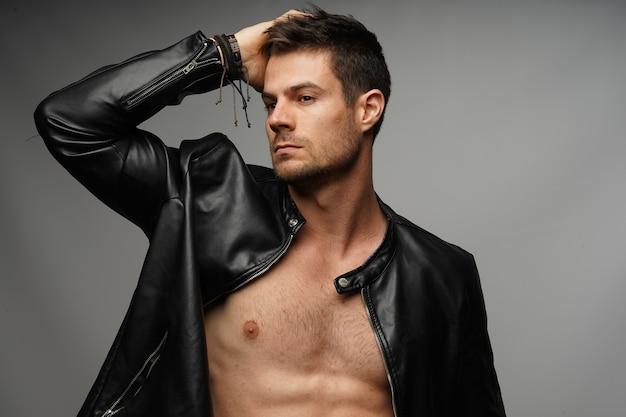 Jovem modelo latino-americano atlético usando uma jaqueta de couro preta e posando contra uma parede cinza