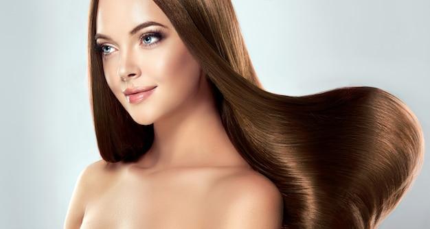 Jovem modelo linda de cabelos castanhos com cabelos longos, lisos e bem tratados
