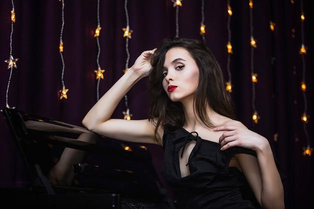 Jovem modelo linda e luxuosa no fundo do piano e luzes elegantes e elegantes
