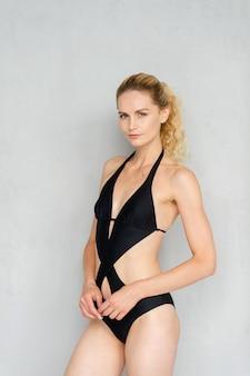 Jovem modelo loira atraente em maiô preto posando