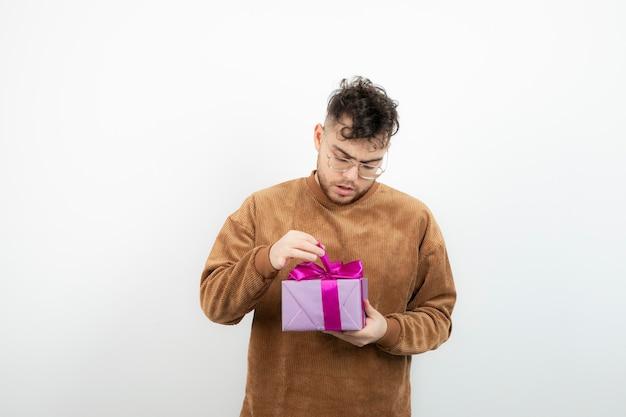 Jovem modelo masculino abrindo presente sobre uma parede branca.