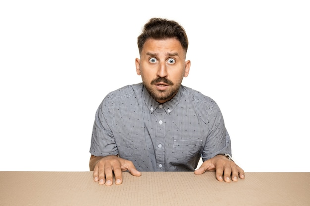 Jovem modelo masculino animado em cima de uma caixa de papelão, olhando para dentro