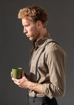 Jovem modelo masculino de lado segurando uma xícara de café