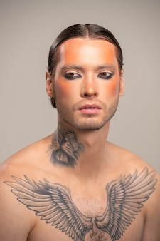 Jovem modelo masculino ou ator de teatro moderno com maquiagem de palco, penteado preciso e tatuagem no peito e pescoço