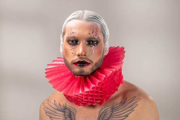 Jovem modelo masculino ou ator do teatro moderno com maquiagem de palco, cabelo branco em penteado preciso e tatuagem no peito olhando para você