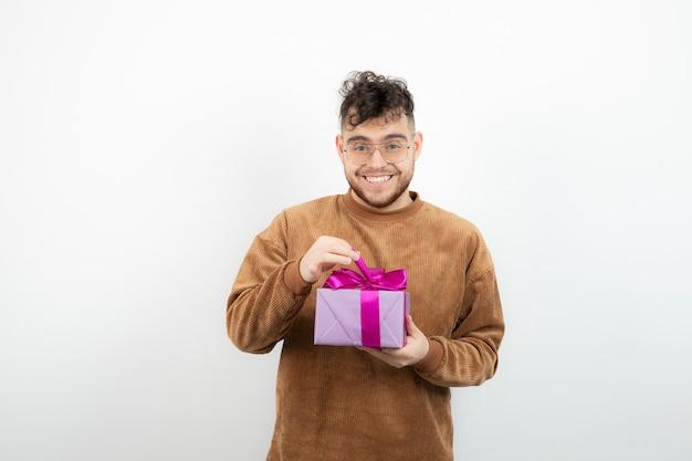 Jovem modelo masculino segurando presente sobre uma parede branca.