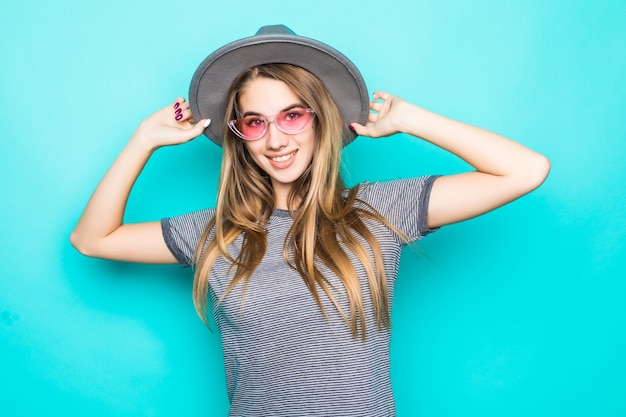 Jovem modelo muito sorridente na moda camiseta, chapéu e óculos transparentes isolados sobre fundo verde